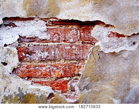 Old destroyed brick wall. Red brickwork in the background of the crumbling plaster. Grunge background for your concept or project. Horizontal location.