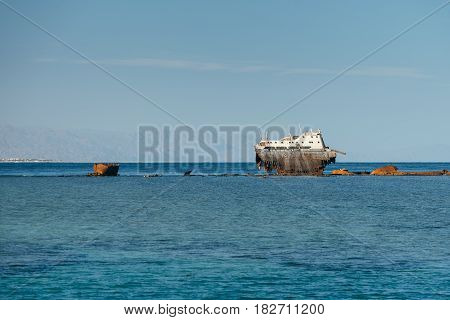 View at rusty shipwreck of a large cargo ship demolished of a storm near coastline of the Red sea.