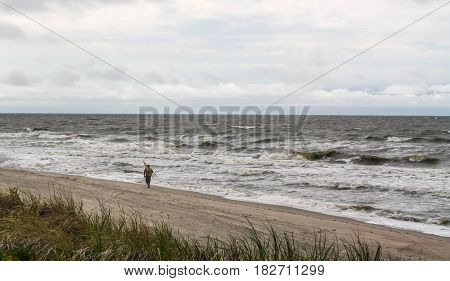 Lonely man on the beach. Amber gathering stormy weather.