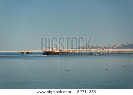 View at the distant pier of a tourist resort. Vacation in Egypt. Summer vacation on Red sea. View at a clear sea with turquoise water in windless conditions. Summer vacation at a sea coastline in an exotic country.