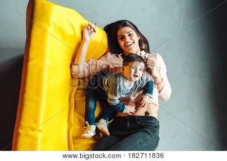 Mother and little son play at home on a yellow couch