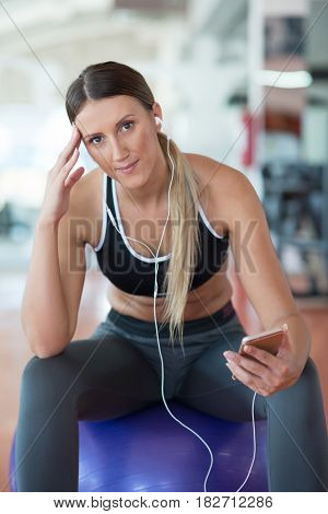 woman setting music on smart phone putting earphones before exercise.