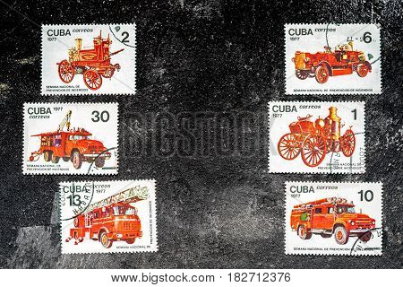 Moscow Russia - April 20 2017: Set of postage stamps printed in Cuba shows fire engines series circa 1977. Copy space for your text on a dark black cement background.