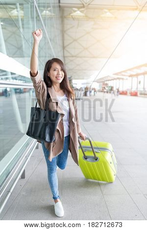 Excited woman go travel with luggage in Hong Kong airport