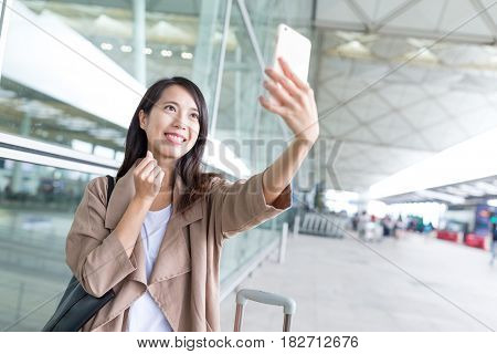 Woman taking selfie by mobile phone with love finger gresture