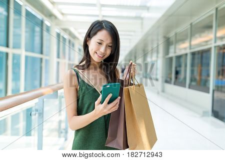 Woman go shopping and using cellphone