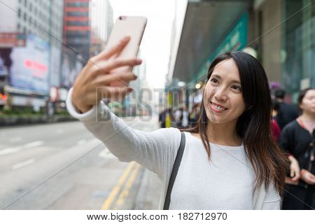 Woman taking selfie with cellphone in Mong Kok city in Hong Kong