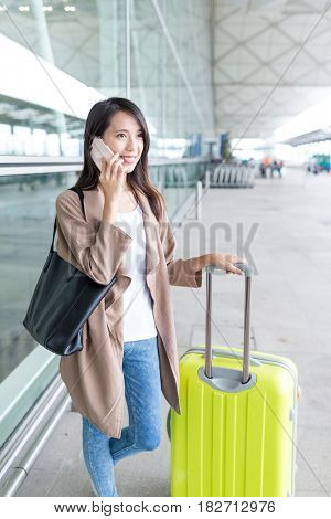 Woman talk to cellphone with her luggage in airport