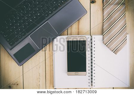 Computer Notebook Necktie and Smartphone on table. Working man desktop concept