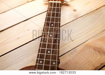 Hawaiian Four-stringed Guitar Ukulele Close-up Frets On Wooden Background