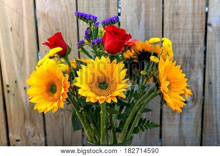 Vase with bouquet of flowers with sunflowers red rose Perez's sea lavender and other