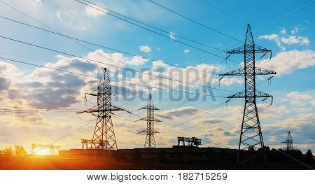 silhouette engineer repair and electrical installation work on high voltage pylons over Blurred construction site. Science Technology Transportation concept.