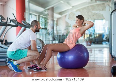 Personal trainer training a woman in the gym with yoga ball.