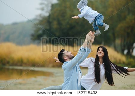 Young family together in nature with a little boy at the lake