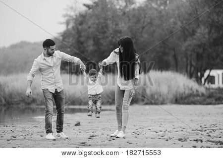 Young family with a little boy walking at the beach in autumn