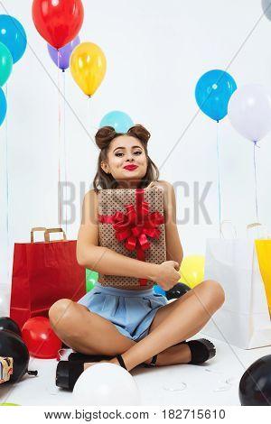 Beautiful girl in pin-up clothing waving kiss looking straight at camera, holding big gift