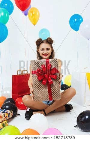 Pretty pin-up girl after cool dress code party showing present box, sitting with balloons