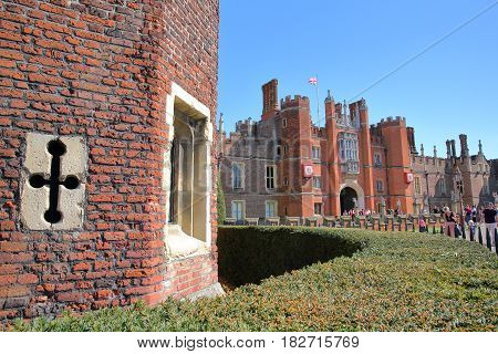 LONDON, UK - APRIL 9, 2017: The West front and main entrance of Hampton Court Palace in Southwest London with details of the red brick stones