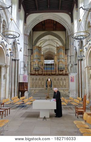 ROCHESTER, UK - APRIL 14, 2017: Interior of the Cathedral with two anglican priests and the organ in the background