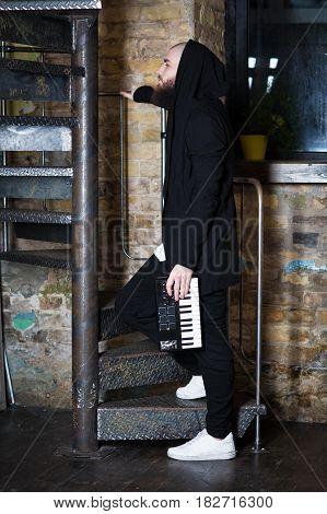 A Bearded Man With A Mini Piano.