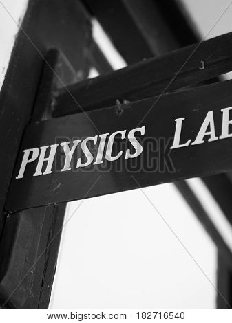 BLACK AND WHITE PHOTO OF BOARD WITH 'PHYSICS LAB' SIGN