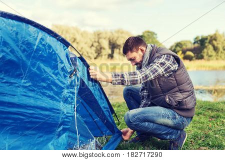 camping, travel, tourism, hike and people concept - happy man setting up tent outdoors