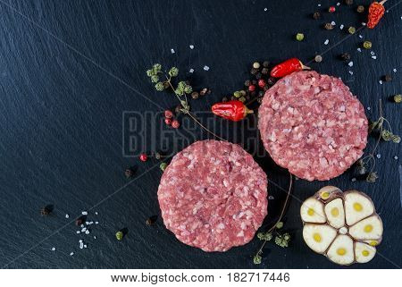 Fresh raw meat burger cutlet on the black slate board with herbs and spices for background. Copy space, top view .