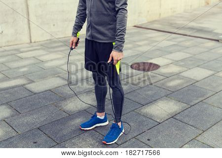 fitness, sport, people, exercising and lifestyle concept - close up of man exercising with jump-rope outdoors