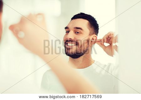 beauty, hygiene and people concept - smiling young man cleaning ear with cotton swab and looking to mirror at home bathroom