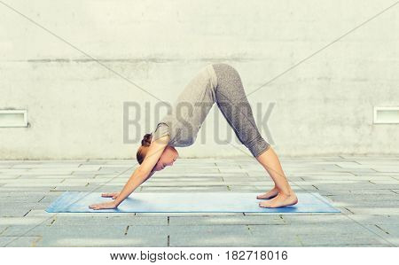 fitness, sport, people and healthy lifestyle concept - woman making yoga in downward facing dog pose on mat over urban street background
