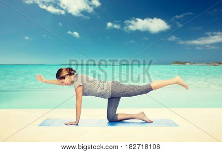 fitness, sport, people and healthy lifestyle concept - woman making yoga in balancing table pose on mat over beach background