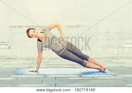 fitness, sport, people and healthy lifestyle concept - woman making yoga in side plank pose on mat over urban street background