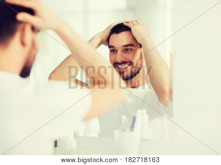 beauty, hygiene and people concept - smiling young man looking to mirror and styling hair at home bathroom