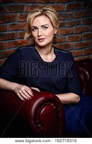 Portrait of a beautiful middle-aged woman in elegant clothes. Business woman sitting on a couch.