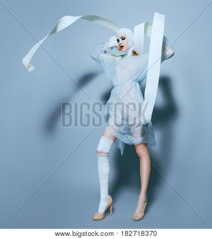 Fashion shot. Gorgeous female model in bandages and hospital gown posing at studio. Beauty and medicine, plastic surgery.