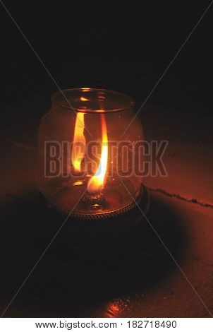Vintage kerosene oil lantern lamp burning with a soft glow light. Kerosene lamp and a candle flickering in the dark
