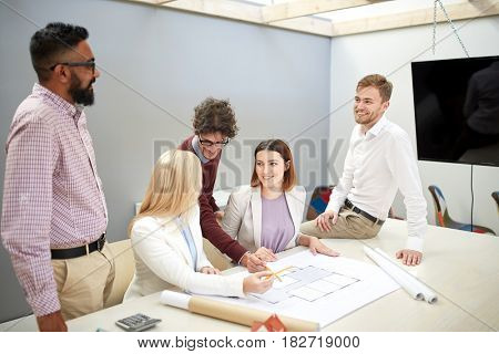 building, construction, architecture, real estate and people concept - happy business team with blueprint meeting and discussing house project at office