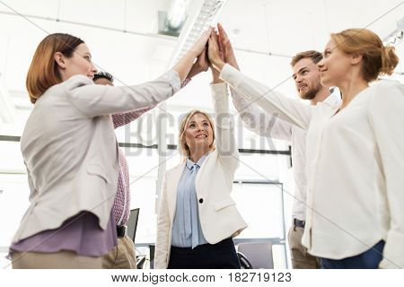 business, startup, gesture, people and teamwork concept - happy creative team making high five at office