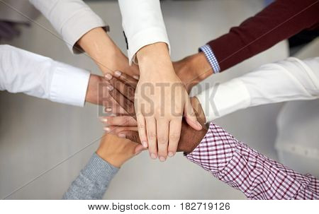 business, startup, gesture, people and teamwork concept - creative team with hands on top of each other at office