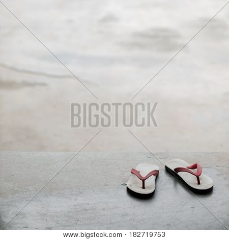 COLOR PHOTO OF PAIR OF FLIP FLOPS ON CONCRETE GROUND