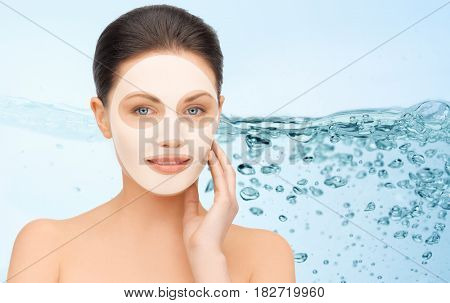 beauty, cosmetology, hydration, people and rejuvenation concept - beautiful young woman with collagen facial mask over blue background and water bubbles
