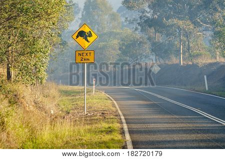 Koala crossing road sign on a smoky country Queensland road. Australia.