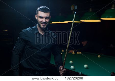Portrait of young caucasian or middle eastern man with cue playing billiard. Green pool table background