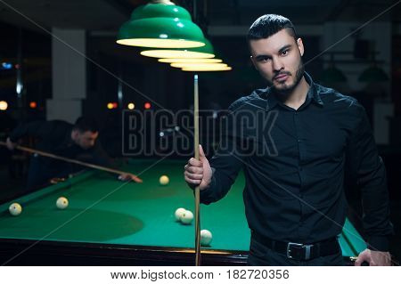 Male friends playing billiard game in club. Young caucasian or middle aestern man standing with cue, green snooker table with balls on background