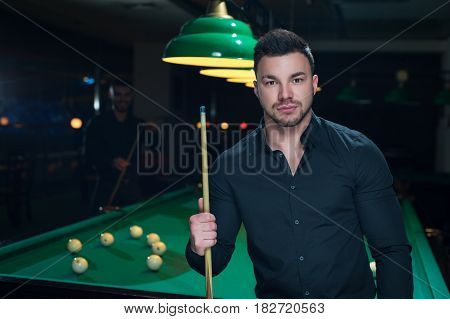Young attractive man with cue. Two male adults playing billiard game in club. Green table with balls background