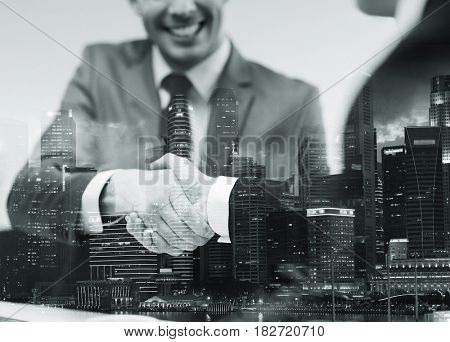 business, cooperation, partnership and people concept - two businessmen shaking hands at office over city buildings and double exposure effect