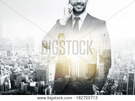 business, technology and people concept - close up of smiling businessman calling on smartphone over city buildings and double exposure effect