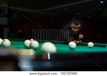 Young handsome man playing billiard game pool alone. Male caucasian or middle eastern adult aiming billiard ball. Shallow depth of field.