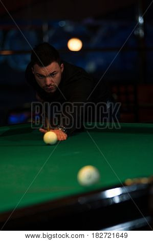 Young caucasian man playing billiard game in club. Male adult aiming to take the snooker shot.