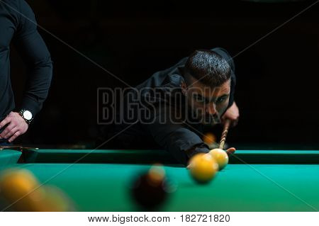 Young man playing billiard in dark club. Male adult aiming to the snooker ball
